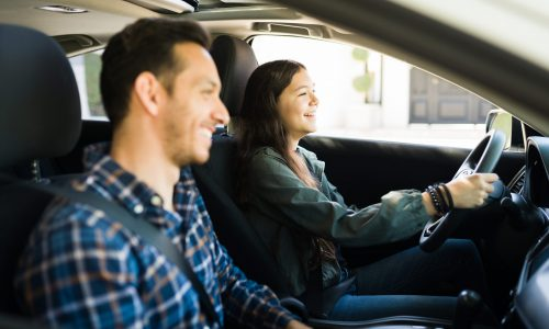 Happy handsome dad and teen daughter laughing while driving. Adolescent girl practicing her driving skills with her father